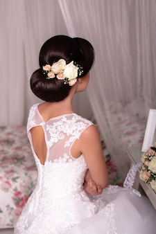 Dos de mariée avec coiffure, robe et fleurs de mariage