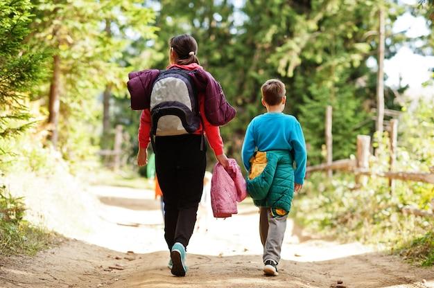 Dos de mère avec trois enfants marchant sur des montagnes boisées. voyages en famille et randonnées avec enfants.
