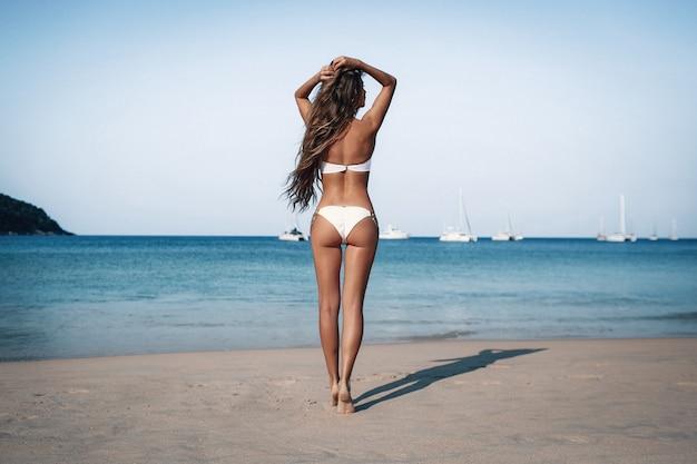 Dos sexy d'une belle femme mince de luxe méconnaissable avec un bronzage parfait et des cheveux bouclés