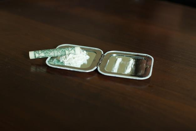 Dose de cocaïne et dollar roulé sur miroir.