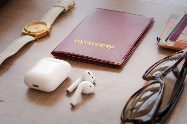 Dosettes blanches, passeport rouge, montre-bracelet, lunettes de soleil brunes, portefeuille, argent liquide