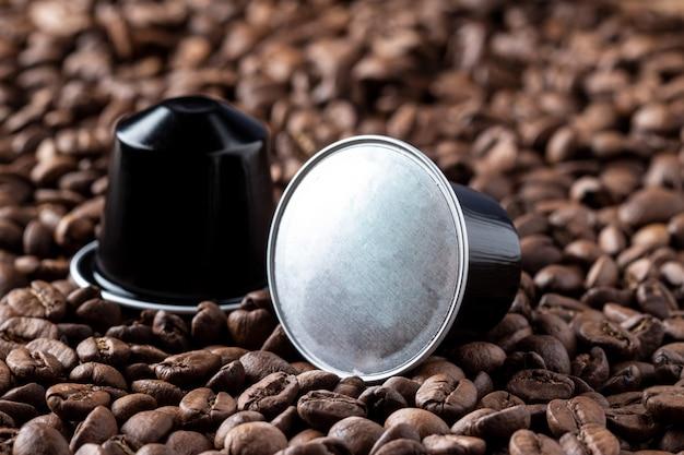 Des dosettes de café sur des grains de café ou des capsules de café