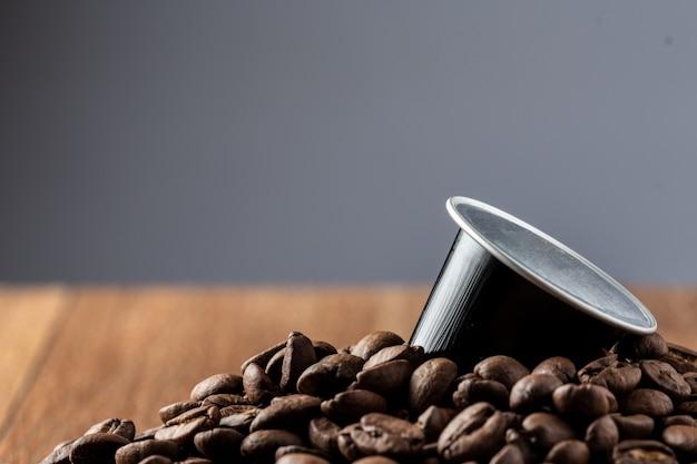 Des dosettes de café sur une table en bois ou une capsula de café em madeira