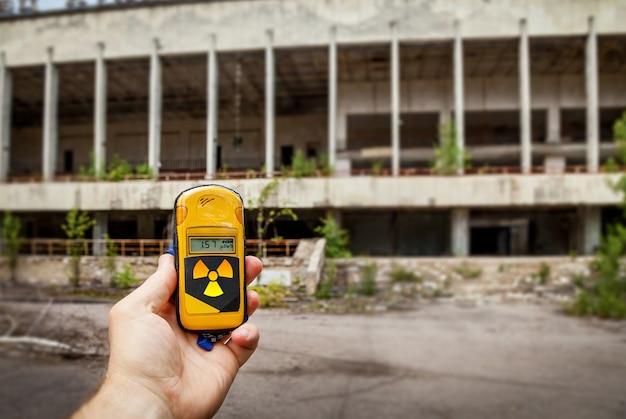 Un dosimètre en mains avec un niveau de radioactivité dans la ville de pripyat, une ville fantôme de la centrale nucléaire de tchernobyl touchée par une catastrophe nucléaire en 1986, zone d'exclusion de tchernobyl, en ukraine.