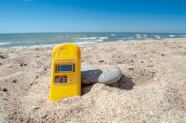 Un dosimètre de rayonnement spécial sur le sable au bord de la mer