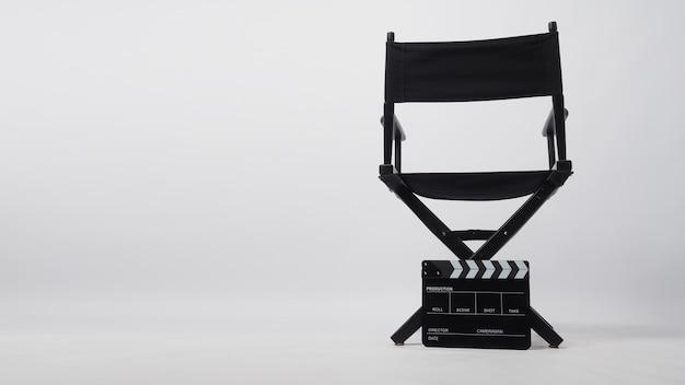 Un dossier de chaise de réalisateur noir avec un panneau de clapet posé sur le sol. il s'agit d'un fond blanc.
