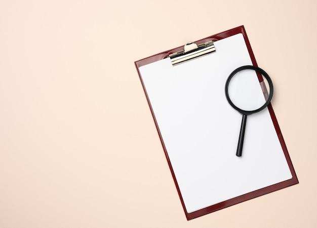 Dossier avec des feuilles blanches vierges et une loupe noire sur une surface beige. surface pour les inscriptions, recherche de solutions et de réponses