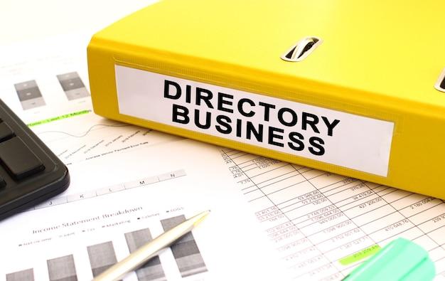 Un dossier jaune avec des documents étiquetés directory business se trouve sur le bureau avec des tableaux financiers