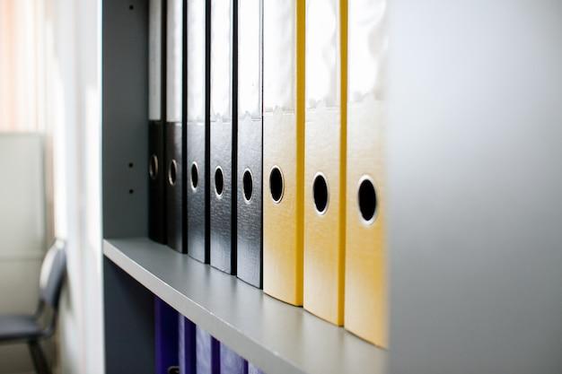 Dossiers d'archives colorés pour les documents sur les étagères du bureau