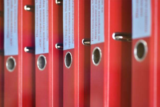 Dossiers de grands dossiers rouges avec des inscriptions pour stocker des documents de bureau