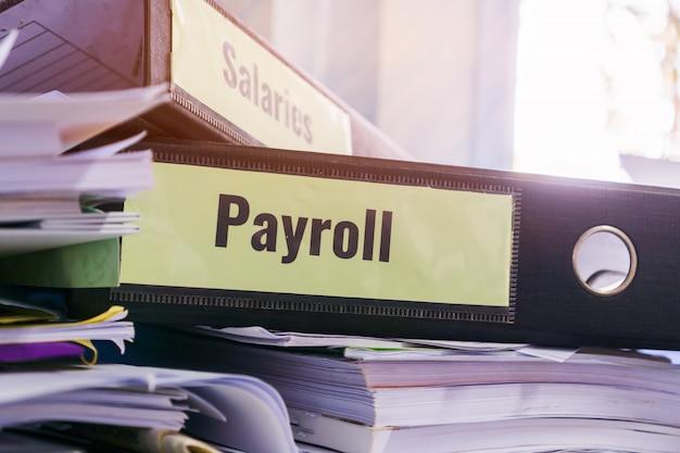 Dossiers de paie et salaires empilés avec étiquette sur classeur noir sur rapport de synthèse des documents