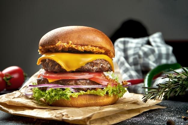 Double burger juteux avec boeuf, tomates, fromage et oignons croustillants sur une table sombre.