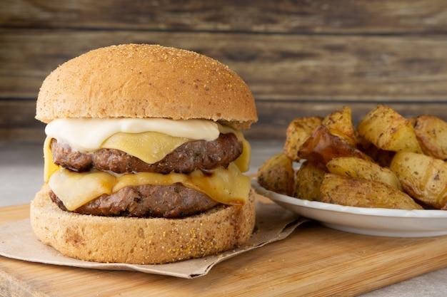 Double cheeseburger sur une planche en bois avec des pommes de terre rôties