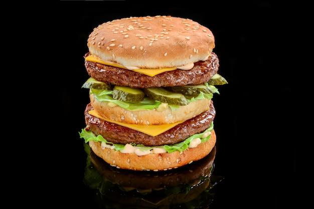 Un double cheeseburger de style classique avec deux galettes de bœuf, sauce, laitue, fromage, cornichons et oignons sur un petit pain aux graines de sésame
