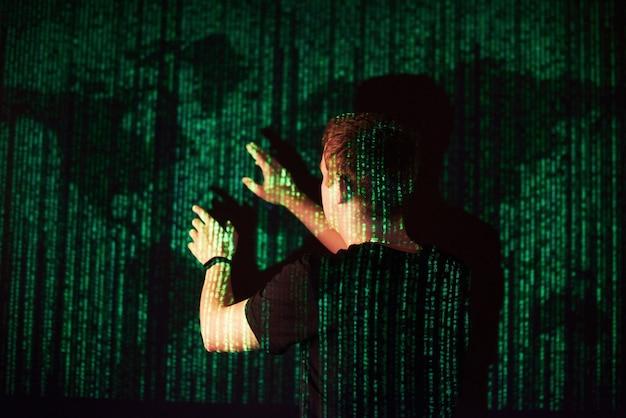 La double exposition d'un homme caucasien et d'un casque de réalité virtuelle vr est vraisemblablement un joueur ou un pirate informatique déchiffrant le code dans un réseau ou un serveur sécurisé, avec des lignes de code, états-unis