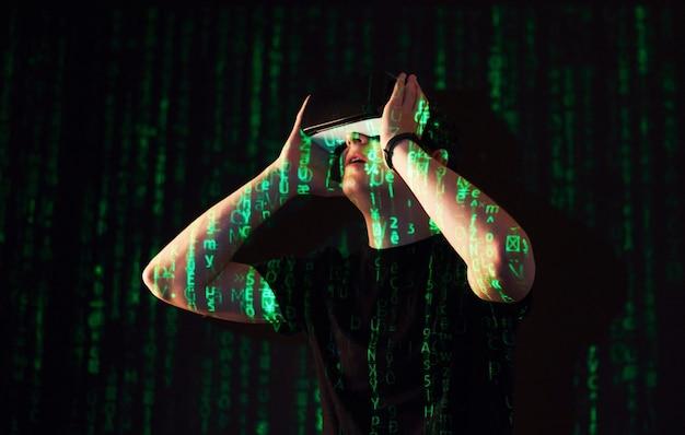 La double exposition d'un homme caucasien et d'un casque de réalité virtuelle vr est vraisemblablement un joueur ou un pirate informatique déchiffrant le code dans un réseau ou un serveur sécurisé, avec des lignes de code en vert