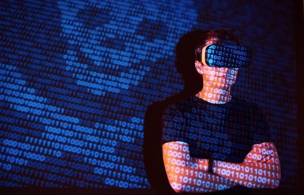 La double exposition d'un homme caucasien et d'un casque de réalité virtuelle vr est vraisemblablement un joueur ou un pirate informatique déchiffrant le code dans un réseau ou un serveur sécurisé, avec des lignes de code
