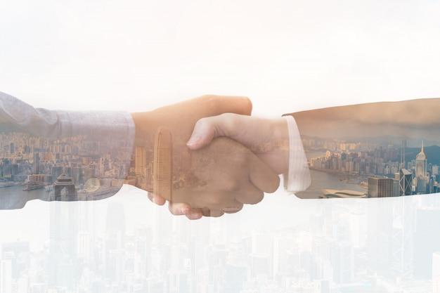 Double exposition d'hommes d'affaires se serrant la main sur fond de ville