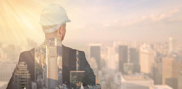 Double exposition d'un ingénieur dans un casque de protection sur fond de ville, métropole. photo de haute qualité
