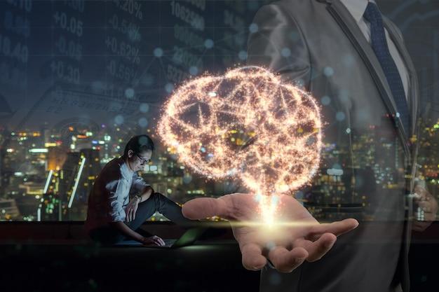 Double exposition de la main d'homme d'affaires tenant la base du cerveau sur l'étincelle sur l'homme d'affaires asiatique