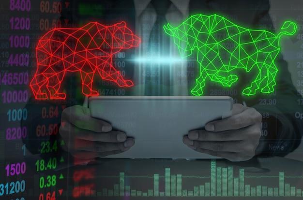 Double exposition de la main d'homme d'affaires tenant l'écriture de forme polygonale de taureau et d'ours