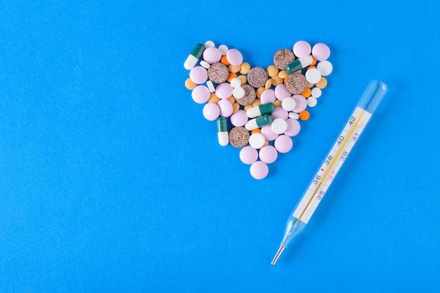 Doublé de pilules pour le coeur et d'un thermomètre pour mesurer la température corporelle sur un bleu.