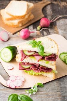 Double sandwich au pastrami et légumes frais et herbes sur une planche à découper. snack américain. style rustique.