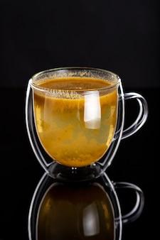 Double tasse en verre avec du thé d'argousier sain fait maison sur une surface noire