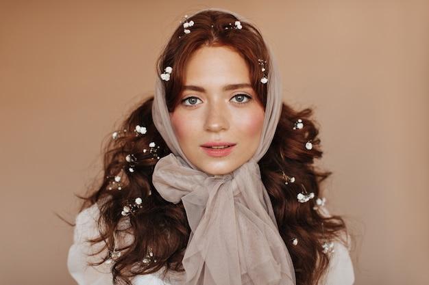 Douce dame avec des taches de rousseur et un fard à joues lumineux posant sur fond beige. femme en casque souriant.