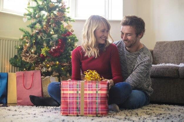 Douce femme ouvrant son cadeau de noël pendant que son garçon la serre dans ses bras