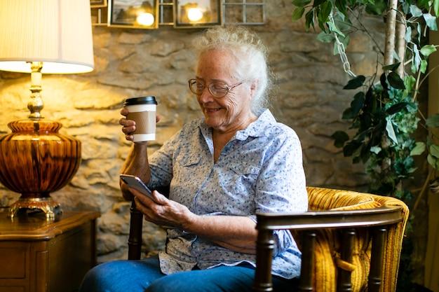 Douce femme senior à l'aide de son téléphone dans un café