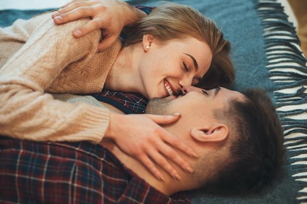 Douce femme avec des taches de rousseur embrasse son mari pendant une matinée froide dans leur appartement