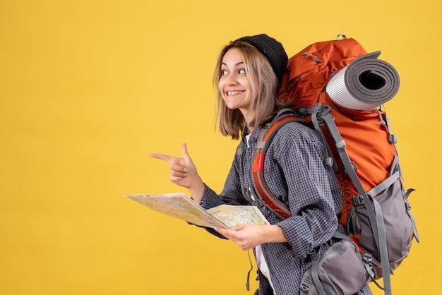 Douce femme voyageuse avec sac à dos tenant la carte pointant le doigt vers la gauche