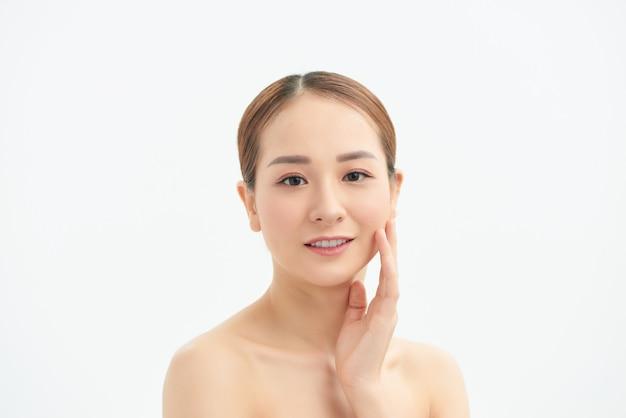 Une douce fille asiatique avec un visage parfait et propre a fermé les yeux avec tendresse touchant la peau