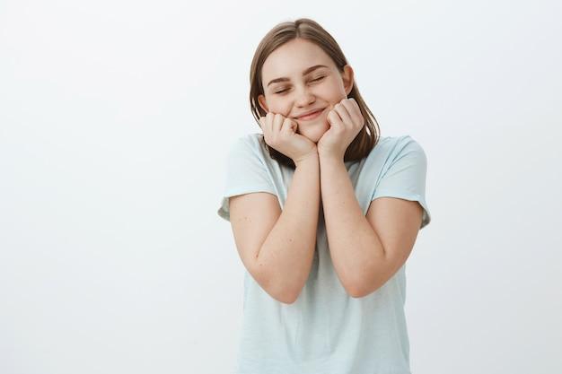 Douce fille mignonne se souvient d'un moment agréable et amusant d'être rêveur et heureux de fermer les yeux de joie souriant largement le visage appuyé sur les mains debout ravi et romantique sur le mur blanc