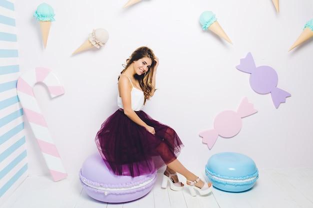 Douce heure d'été heureuse de jolie jeune femme à la mode en jupe en tulle assis sur un énorme macaron. couleurs pastel, bonbons, délicieux, appréciant, bonheur, souriant, relaxant.
