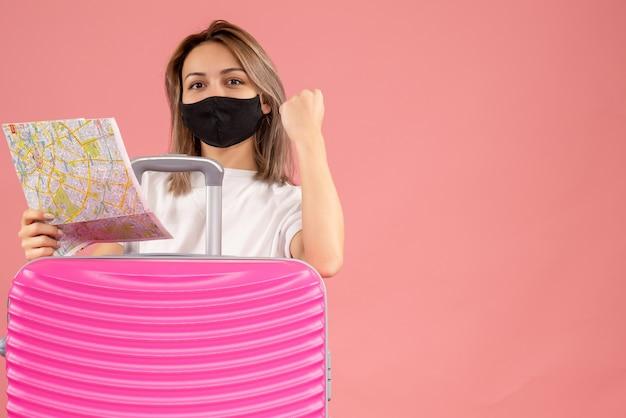 Douce jeune femme avec un masque noir tenant une carte derrière une valise rose