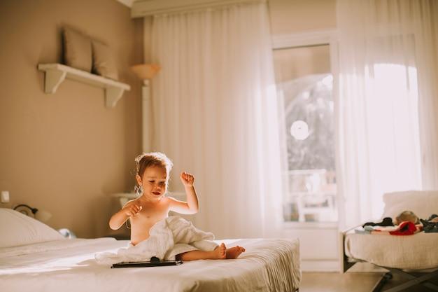 Douce petite fille bouclée avec une serviette sur son corps humide dans une chambre après la douche