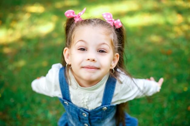 Douce petite fille à l'extérieur avec des cheveux bouclés dans deux longues queues, gros plan