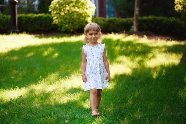 Douce petite fille avec hétérochromie deux yeux colorés à l'extérieur avec des cheveux bouclés dans le vent.