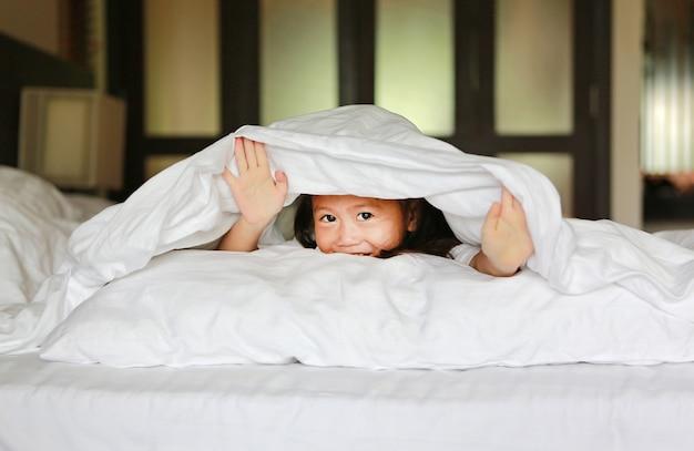 Douce petite fille regardant la caméra et souriant en position couchée sous la couverture