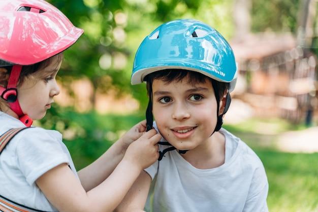 La douce petite soeur aide son frère à attacher son casque de protection. les enfants s'amusent à l'extérieur