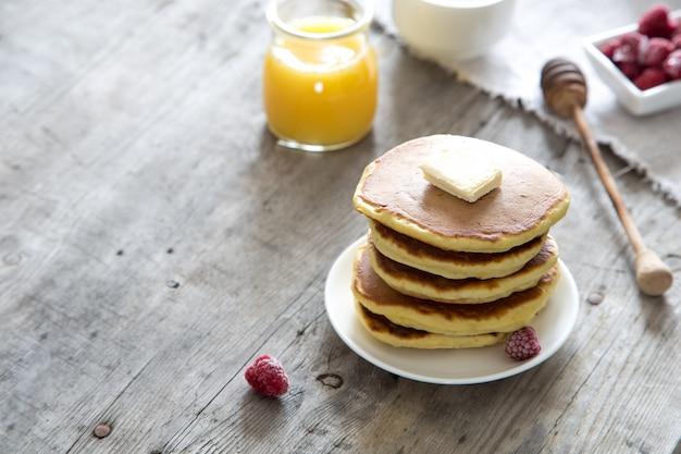 Douce pile de crêpes maison avec beurre, framboises et miel au petit-déjeuner