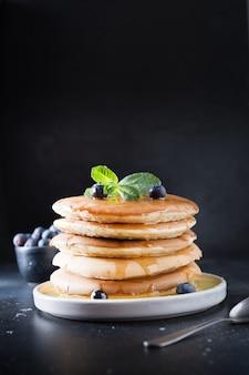 Douce pile maison de crêpes aux myrtilles fraîches et à la menthe dans une assiette moderne sur fond noir.