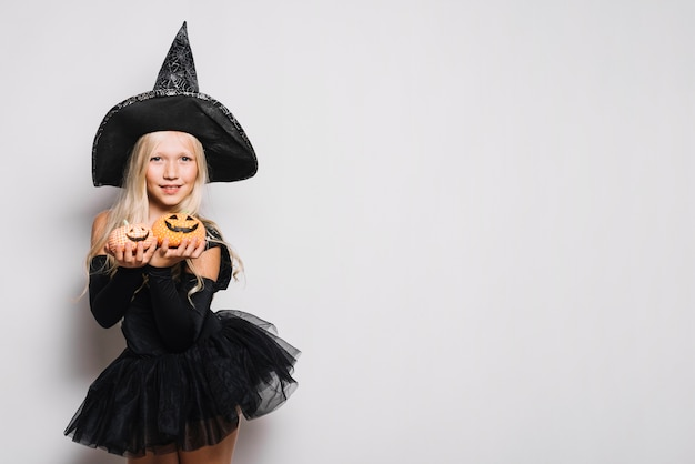 Douce sorcière montrant des citrouilles