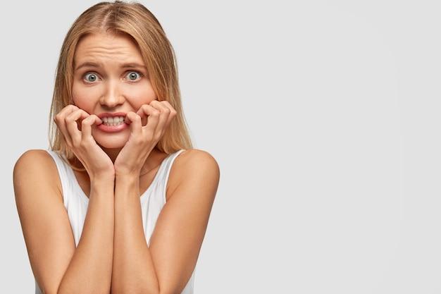 Douce tendre belle femme blonde regarde avec anxiété la caméra, garde les mains près des dents serrées, a une expression nerveuse