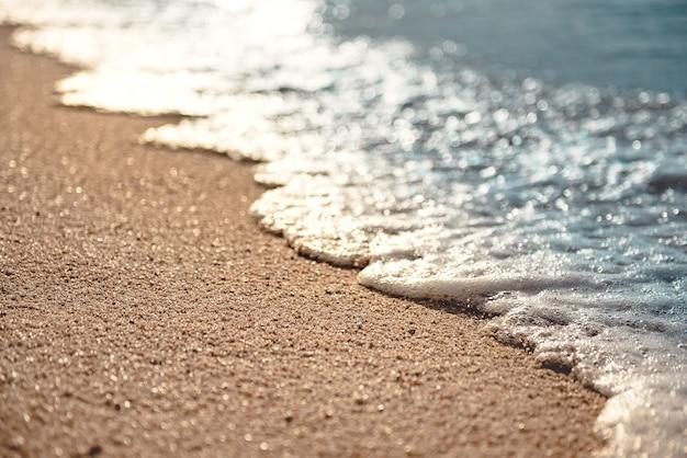 Douce vague de la mer sur la plage de sable