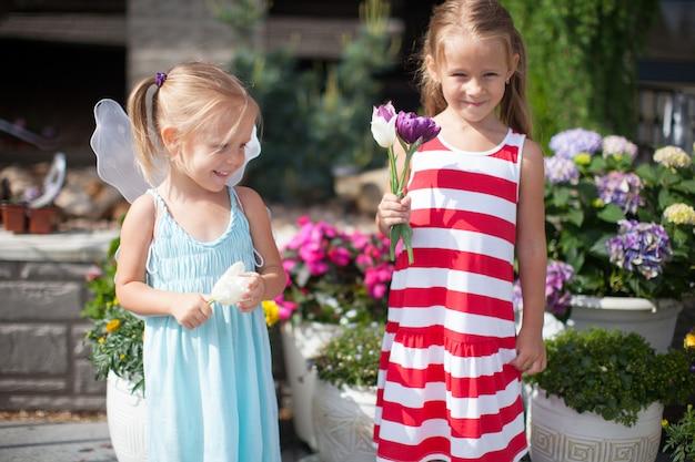 Douces petites filles dans une cour de pays avec des fleurs dans leurs mains