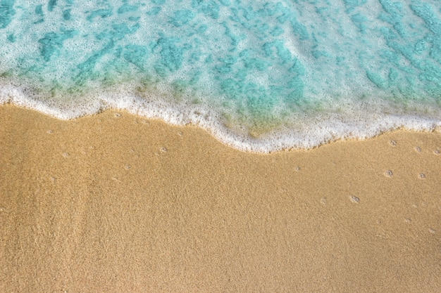Douces vagues bleues avec l'écume de l'océan sur le fond de la plage de sable fin.