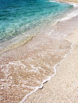 Douces vagues de la mer bleue transparente sur la plage de sable fin